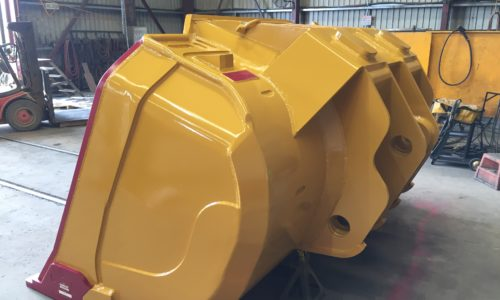 Underground loader bucket - Side view of an Outcast bucket that is ready to dig without any heel shrouds. Also shows external ears for attaching the bucket to the loader machine.
