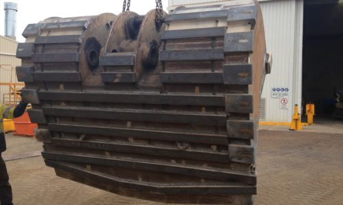 Underside view of conventional underground loader bucket with wear bars and heel blocks attached.