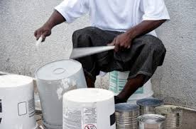 Man playing music using plastic buckets in place of drums