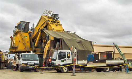 Two boilermaking service trucks providing equipment for servicing Komatsu PC8000 shovel during day shift